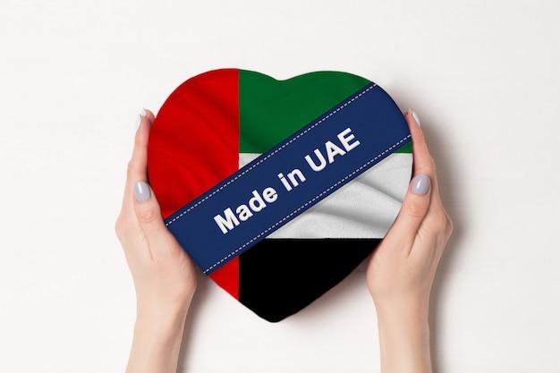 アラブ首長国連邦で作られた碑文は、アラブ首長国連邦の旗。ハート型のボックスを保持している女性の手 Premium写真