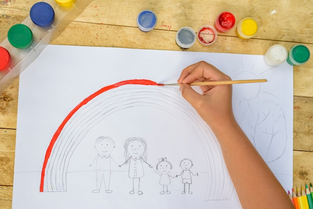 子供の手は、ブラシと絵の具で絵を描きます。上面図 Premium写真