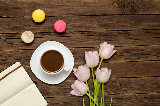 一杯のコーヒー、マカロン、ピンクのチューリップ、木製の背景上のノートブック。上面図 Premium写真