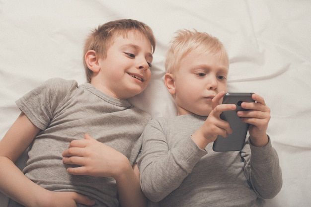 スマートフォンでベッドに横たわっている男の子 Premium写真