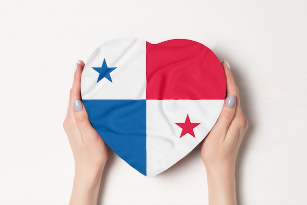 女性の手でハート型ボックスにパナマの旗。 Premium写真