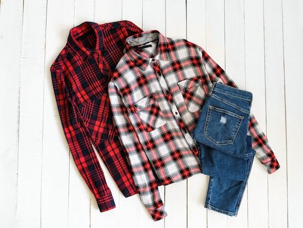 Концепция одежды. две клетчатые рубашки и джинсы на деревянном фоне. вид сверху Premium Фотографии