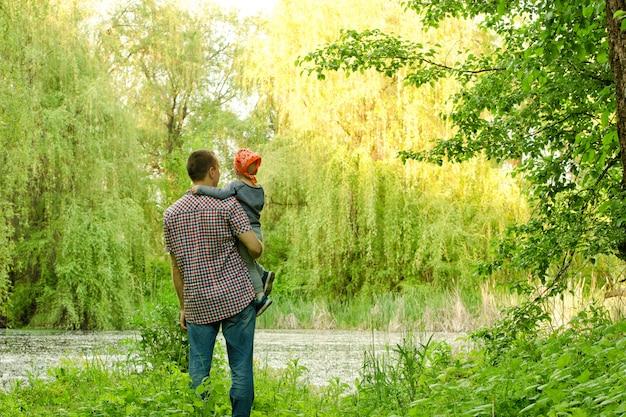 森の湖の近くに小さな息子とお父さんが立っています。 Premium写真