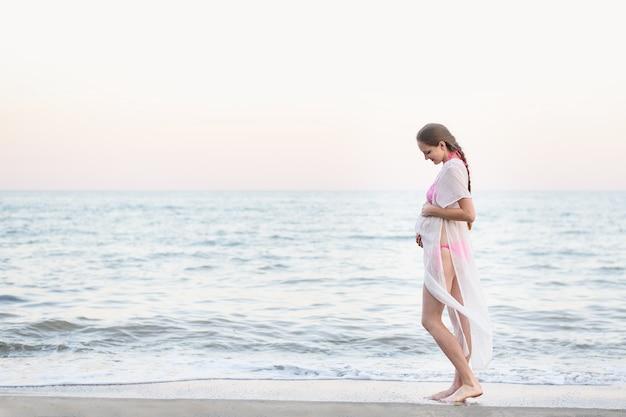 Молодая беременная женщина стоит на берегу моря и обнимает ее живот. наслаждаясь моментом. Premium Фотографии