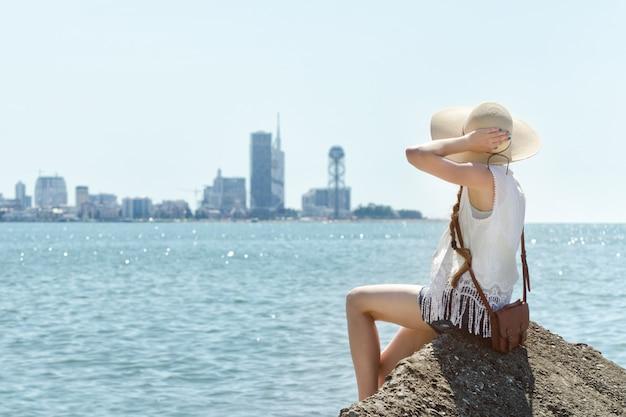 Девушка в шляпе, сидя на скале у моря. город на расстоянии. солнечный день Premium Фотографии
