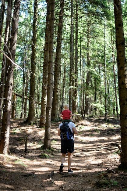 バックパックと針葉樹林の上を歩く彼の肩の若い息子を持つ父。背面図。アクティビティと観光 Premium写真