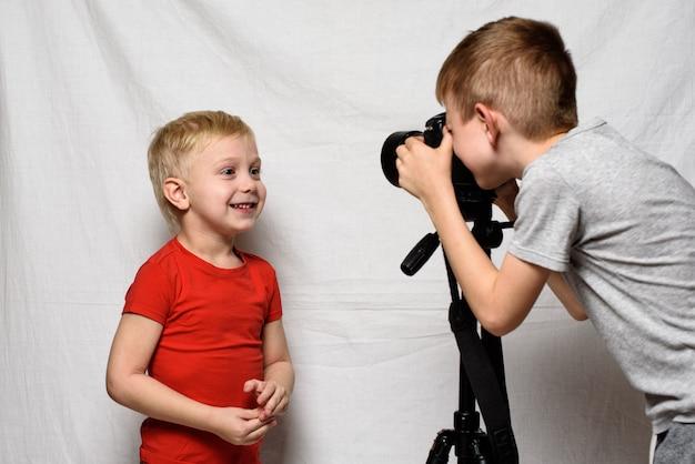 少年たちは一眼レフカメラでお互いを撮影しています。ホームスタジオ。若いブロガー Premium写真