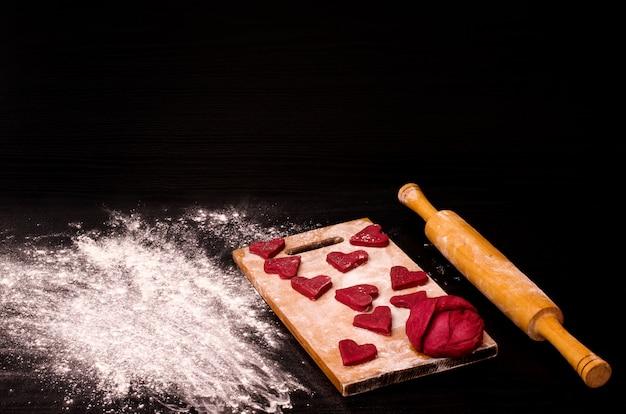 Красное сердечное печенье и кусок теста на деревянной доске, выпечка на день святого валентина Premium Фотографии
