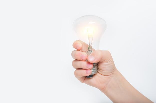 明るい背景に子供の手に輝く白熱灯 Premium写真