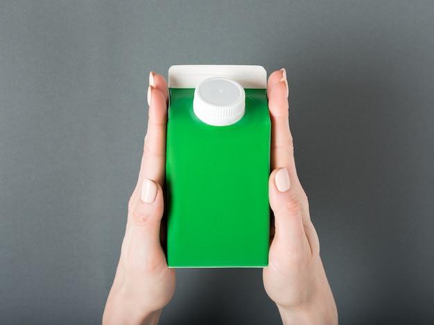 緑のカートンボックスまたはテトラパックのパッケージに女性の手でキャップ。 Premium写真