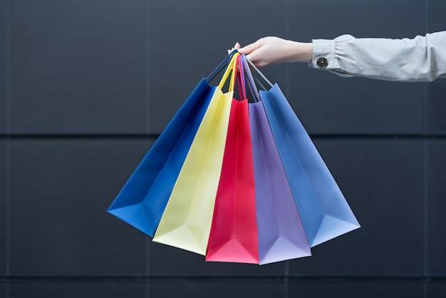 Пять цветных сумок для покупок в женской руке. Premium Фотографии