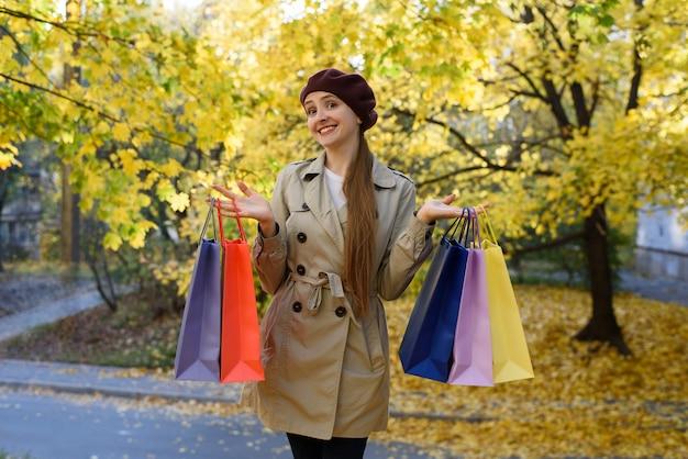 モールの近くのカラフルなバッグと幸せな若い女性中毒者。 Premium写真
