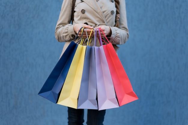 Пять цветных сумок для покупок в женских руках. Premium Фотографии
