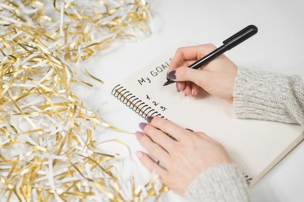 Женские руки, написание мои цели в записной книжке. Premium Фотографии