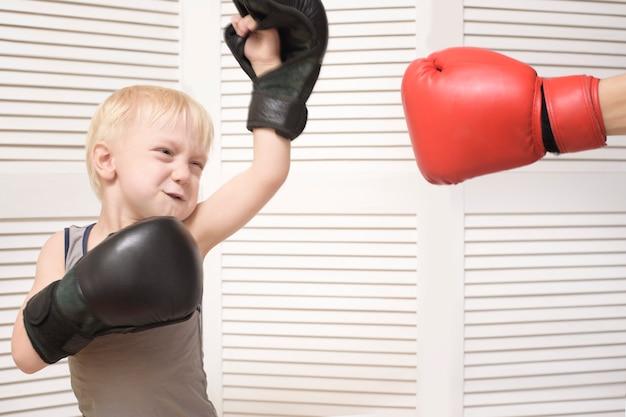 金髪の少年は赤い手袋で手でボクシングします。感情 Premium写真