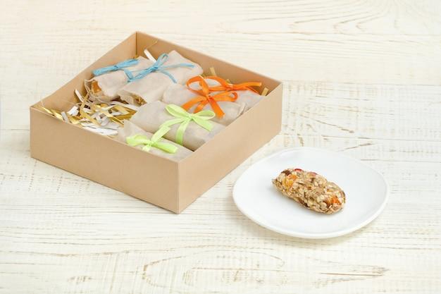 ソーサー上のバーのミューズリーとバー付きの箱。白い木製テーブル Premium写真