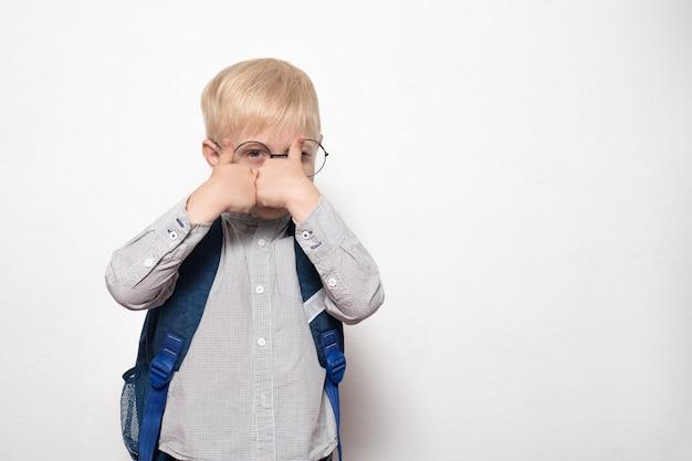 メガネと学校のバックパックを持つ金髪の少年の肖像画は、ジェスチャークラスを示しています。学校のコンセプト Premium写真