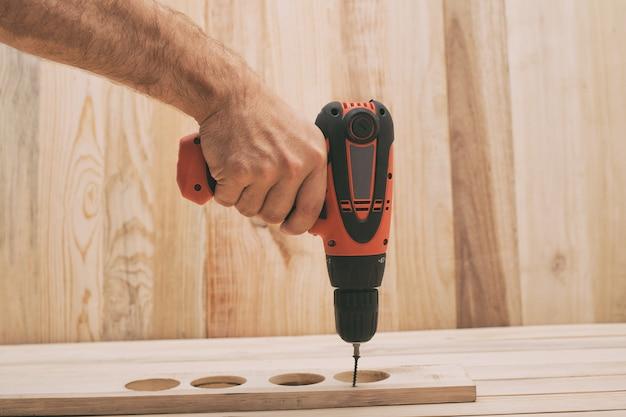 男性の手で電動ドリルドライバー。ネジを締め、薄茶色の木製テーブルでワークを加工します。 Premium写真