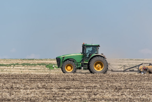 青い空を背景に地面を耕すトラクター Premium写真