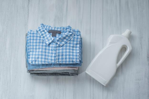 折り畳まれたシャツと洗剤のボトルのスタック。上面図 Premium写真