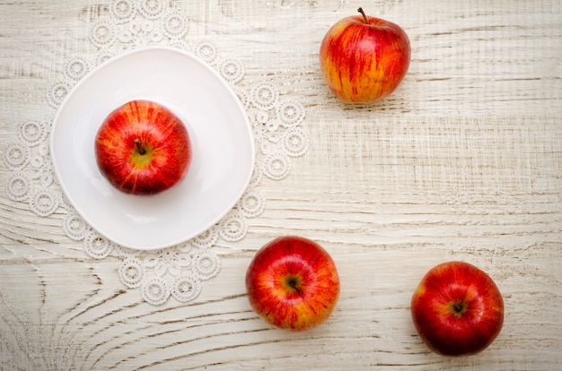 Яблоко на блюдце спелых яблок Premium Фотографии