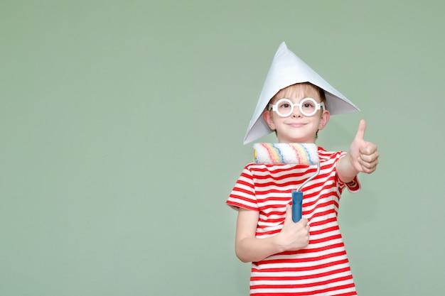 Мальчик в бумажной шляпе и очках показывает круто. портрет. ролик для покраски Premium Фотографии