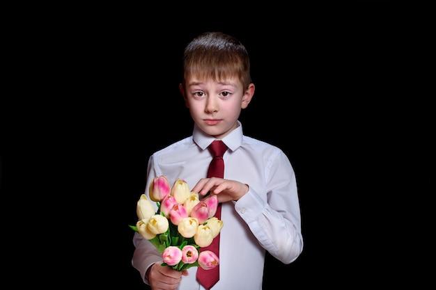 チューリップの花束と白いシャツでかわいい男の子。黒に分離 Premium写真