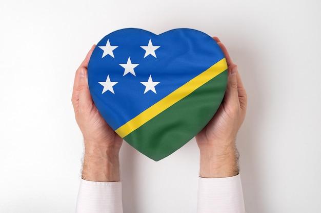 男性の手でハート形ボックスにソロモン諸島の旗。 Premium写真