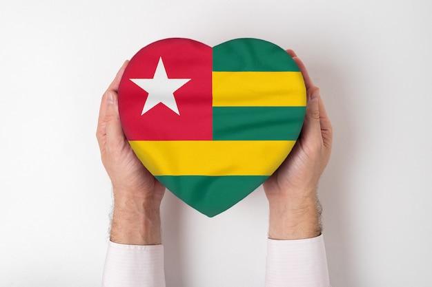 男性の手でハート形のボックスにトーゴの旗。 Premium写真