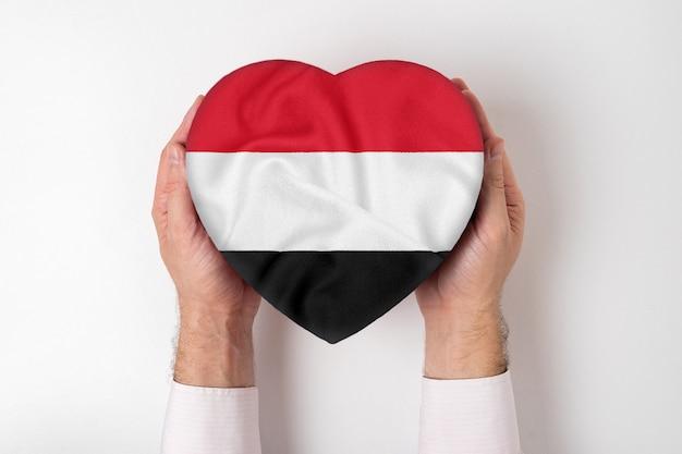 男性の手でハート形のボックスにイエメンの旗。 Premium写真