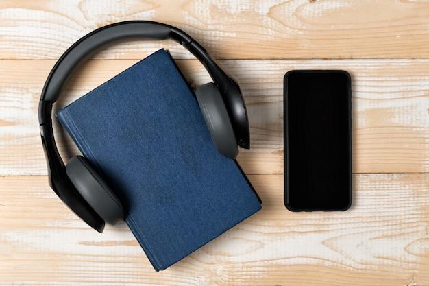 Телефон, книга и наушники на светлом деревянном фоне. концепция электронных книг и аудио книг. вид сверху Premium Фотографии