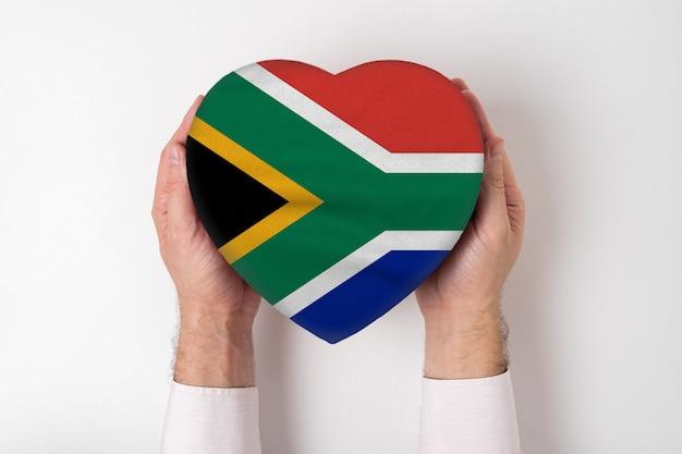 男性の手でハート型ボックスに南アフリカ共和国の旗。 Premium写真