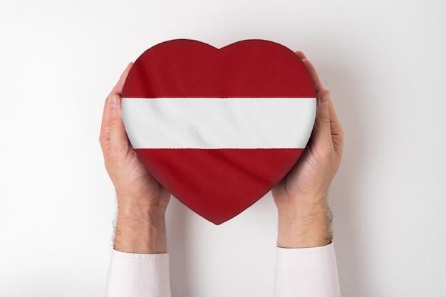 男性の手でハート形ボックスにラトビアの旗。 Premium写真