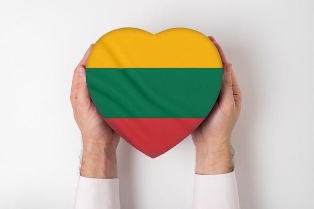 男性の手でハート形のボックスにリトアニアの旗。 Premium写真