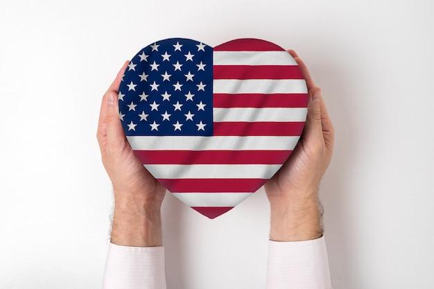 男性の手でハート型ボックスに米国の旗。 Premium写真