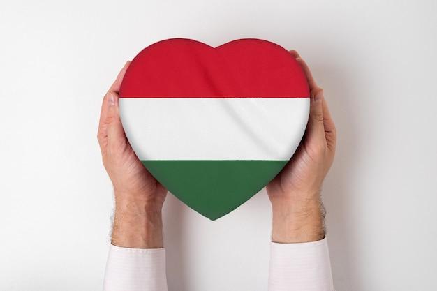 男性の手でハート型ボックスにハンガリーの旗。 Premium写真
