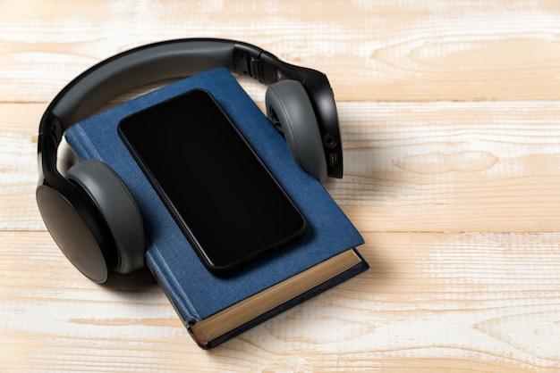 ヘッドフォンで本の携帯電話。オーディオブックのコンセプトです。軽い木製の背景。 Premium写真