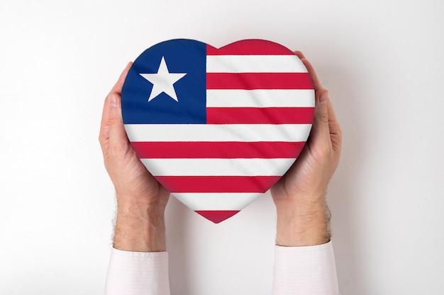 男性の手でハート型のボックスにリベリアの旗。白色の背景 Premium写真