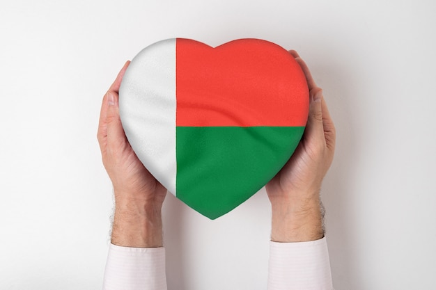 男性の手でハート型のボックスにマダガスカルの旗。白色の背景 Premium写真