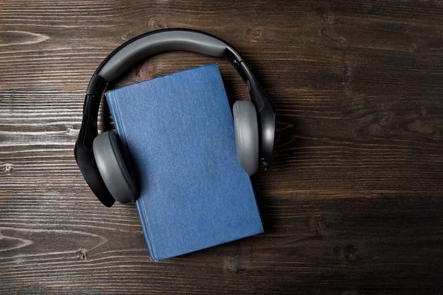 本のヘッドフォン。オーディオ学習の概念。暗い背景の木。コピースペース、トップビュー Premium写真