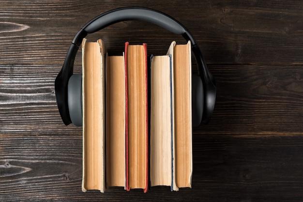 木製の背景上の古い本のスタックで着用のヘッドフォン。お気に入りのオーディオブックのコンセプト。上面図 Premium写真