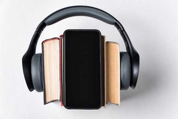 ステレオヘッドフォン、書籍、白い背景の上の電話。オーディオブックのコンセプトです。コピースペース Premium写真