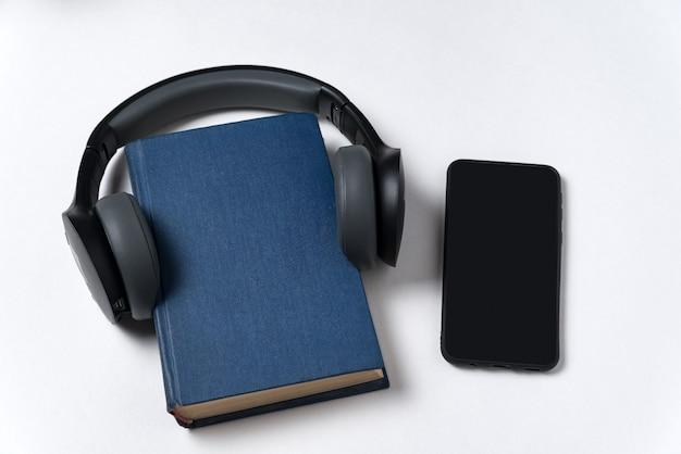 本、ヘッドフォン、白い背景の上の電話。スマートフォンで本を聴きます。オーディオブックのコンセプトです。 Premium写真