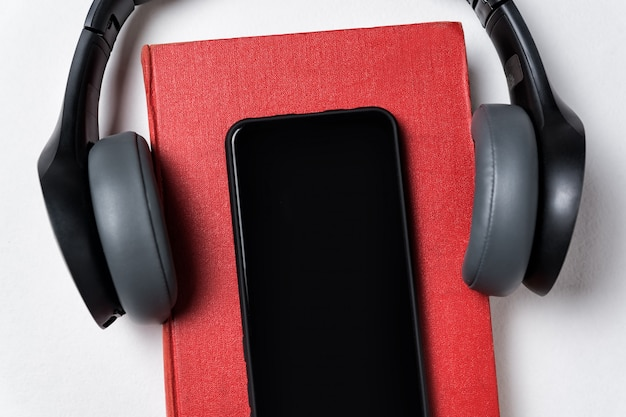 イヤホン、本、白い背景の上の携帯電話。本やオーディオブックのコンセプトです。コピースペース、クローズアップ Premium写真