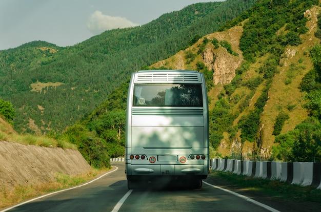Задняя сторона автобуса. вид сзади. пустой белый автобус на горном шоссе. Premium Фотографии