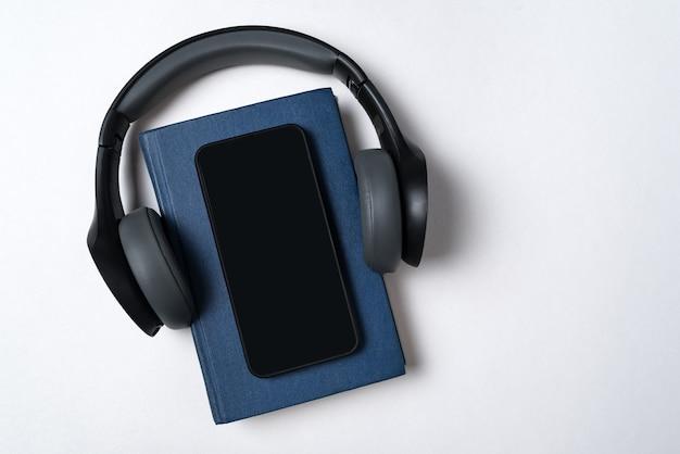ブルーブック、ヘッドフォン、電話。電子書籍とオーディオブックのコンセプト。白い背景のコピースペース。 Premium写真