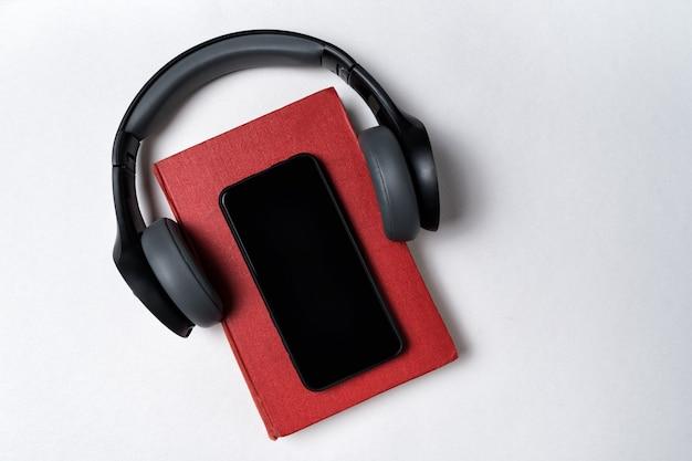 それらを置くヘッドフォンで白い背景に予約します。電子書籍やオーディオブックのコンセプト。トップビューコピースペース Premium写真