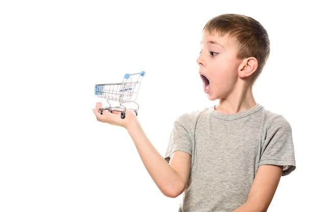 Удивлен мальчик с открытым ртом, держа маленький металлический корзина на ладони. Premium Фотографии