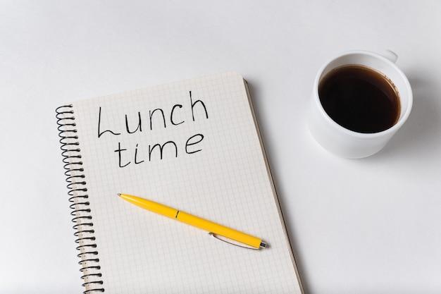 Тетрадь с надписью время обеда. чашка кофе и ручка на белом фоне Premium Фотографии