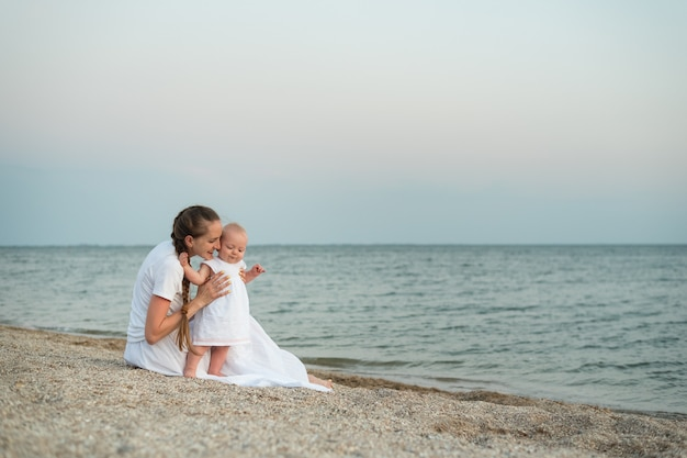 Молодая мать и ребенок, сидя на песчаном пляже. морской отдых с маленькими детьми Premium Фотографии
